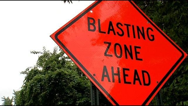 A sign warns motorists driving near construction of the East End Bridge that blasting is taking place.