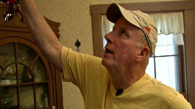 Bob Hill points to a crack in the ceiling of his home he says was caused by blasting as crews continue construction on the East End Bridge.