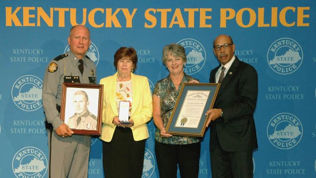 Public Safety Cabinet Secretary J. Michael Brown (right) and KSP Commissioner Rodney Brewer (left) presented the award to Barbara Teague (second from left) and Phyllis McGuire (second from right).