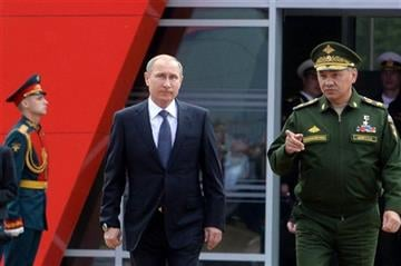 (Vasily Maximov/ pool photo via AP). Russian President Vladimir Putin, center, and Defense Minister Sergei Shoigu, right, arrive for the opening of the Army-2015 international military show in Kubinka, outside Moscow, on Tuesday, June 16, 2015.