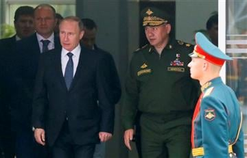 (Maxim Shemetov/Pool photo via AP). Russian President Vladimir Putin, left, and Defense Minister Sergei Shoigu, right, arrive to attend the opening of the Army-2015 international military show featuring the latest Russian weapons in Kubinka.