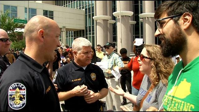 LMPD officers speak with activists during a protest in downtown Louisville on June 22, 2015.