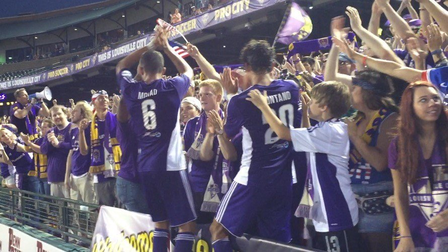 Tarek Morad and Enrique Montano celebrate with fans after Louisville City defeated Richmond 3-0 on Saturday, July 4, 2015.