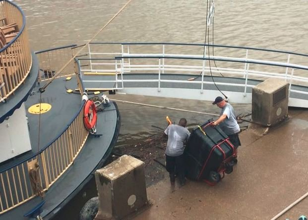 This photograph from Tara Kleinhenz shows two city employees dumping trash into the Ohio River.