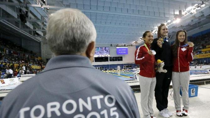 Louisville swimmer Kelsi Worrell (center right) celebrates her Pan Am Games gold medal. (AP photo.)