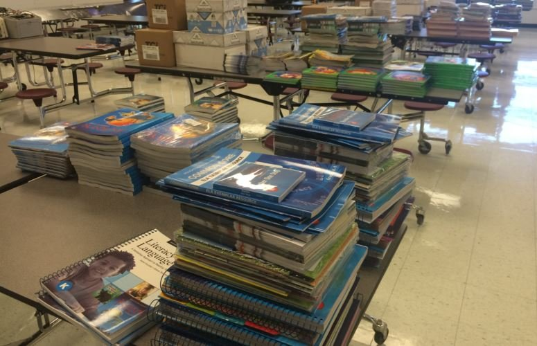 Workbooks and textbooks are sorted by grade level in the cafeteria of Alex R. Kennedy Elementary School (Photo by Toni Konz, WDRB News)