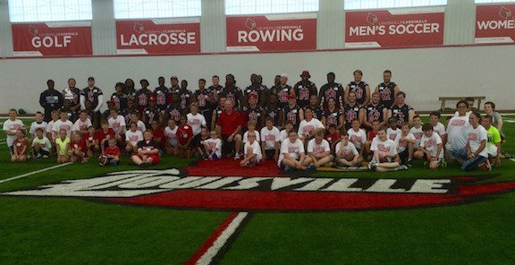 Louisville players and kids pause for a team picture before a clinic sponsored by the Petrino Family Foundation. (WDRB photo by Eric Crawford).