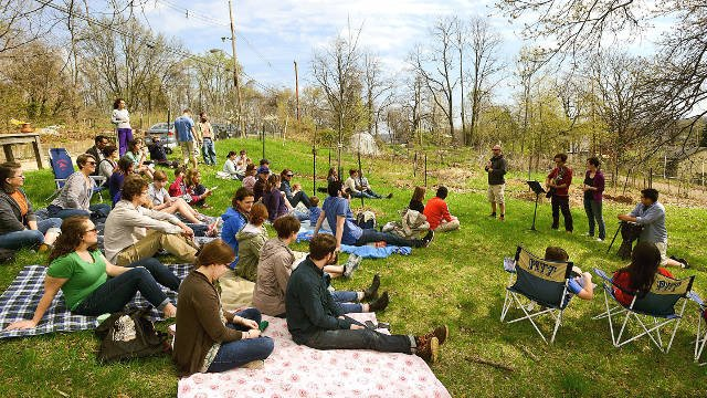 Members of the Open Door Church at Garfield Community Farm gather under budding trees to worship in the open air in Pittsburgh, Pennsylvania. (Bob Donaldson/Post-Gazette)