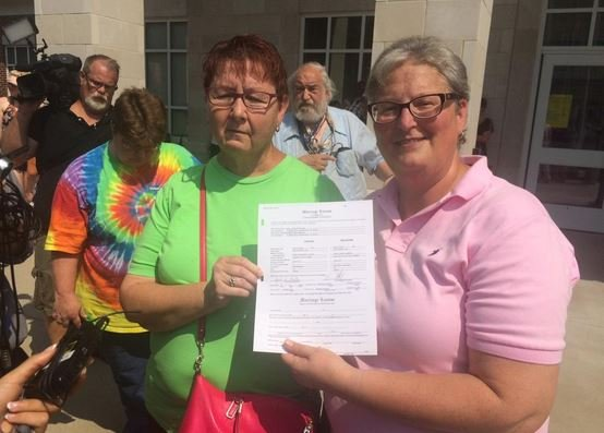 April Miller and Karen Roberts hold their marriage license outside the Rowan County Courthouse on Friday (Photo by Toni Konz, WDRB News)