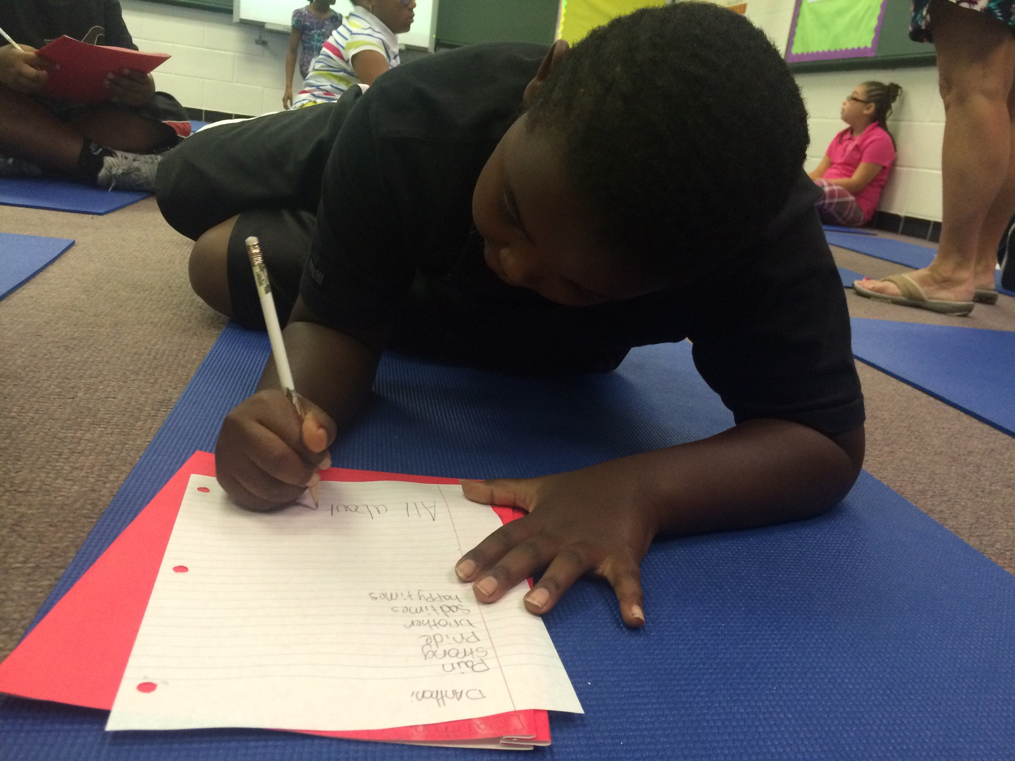 D'Anthoni Vaughn, 9, writes down words describing how he feels as he listens to a song (Photo by Toni Konz, WDRB News)