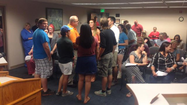 Dennis Martin speaks with some of his current and former students during a recess in the board meeting Sept. 10, 2015.