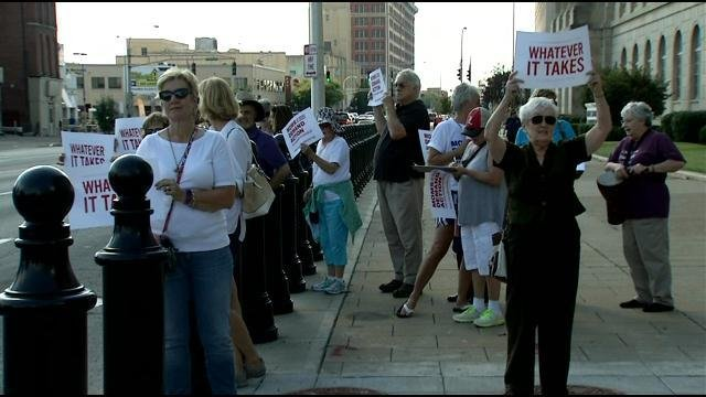 """In Louisville, about two dozen people rallied outside the Federal Building with signs that read """"every town for gun safety."""""""