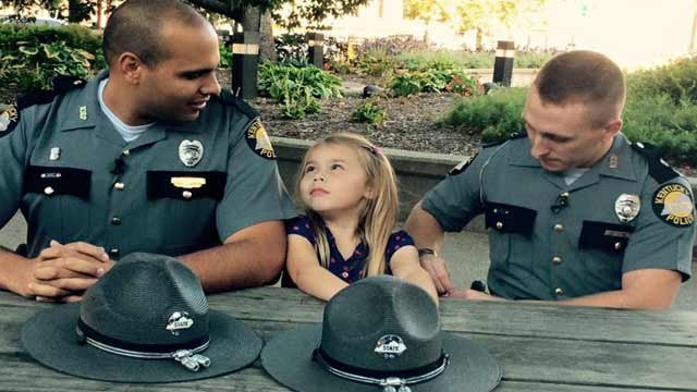 KSP Trooper Eric Homan and KSP Trooper Pat Hamilton chat with Isabella Gregory, 5, during a visit to Louisville on Tuesday. (Photo by Toni Konz, WDRB News)