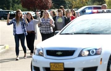 (Michael Sullivan/The News-Review via AP). Students, staff and faculty are evacuated from Umpqua Community College in Roseburg, Ore. Thursday, Oct. 1, 2015, after a deadly shooting.