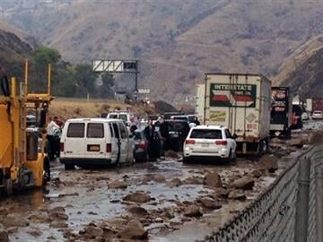 (Caltrans via AP). In this photo provided by Caltrans, vehicles are stopped in mud on California's Interstate-5 after flooding Thursday, Oct. 15, 2015.