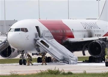 (AP Photo/Wilfredo Lee). Firefighters walk past a Dynamic Airways Boeing 767, Thursday, Oct. 29, 2015, at Fort Lauderdale/Hollywood International Airport in Dania Beach, Fla. The passenger planes' engine caught fire Thursday.