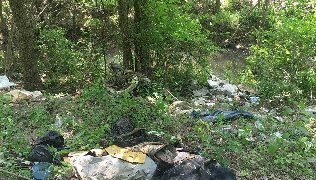 Crime scene tape hangs in the trees at the camp on Monday, May 11, 2015, which is located where Mill Creek meets the railroad tracks in Shively. (WDRB File Photo)