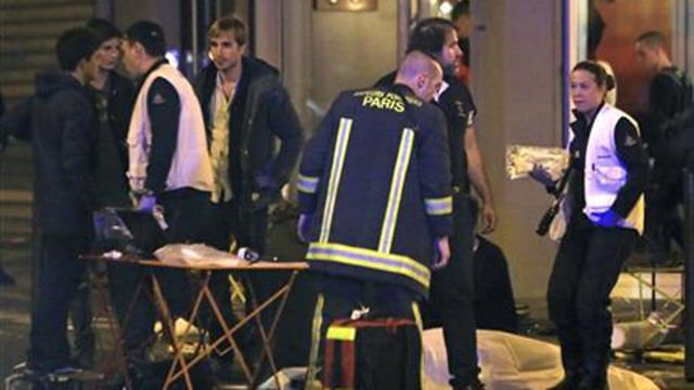 Rescue workers at the scene as victims lay on the pavement outside a Paris restaurant, Friday, Nov. 13, 2015. (AP Photo/Thibault Camus)