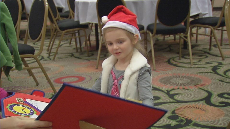 Chloe Beth Lane, who dad is deployed, looks at her gifts from Amazon