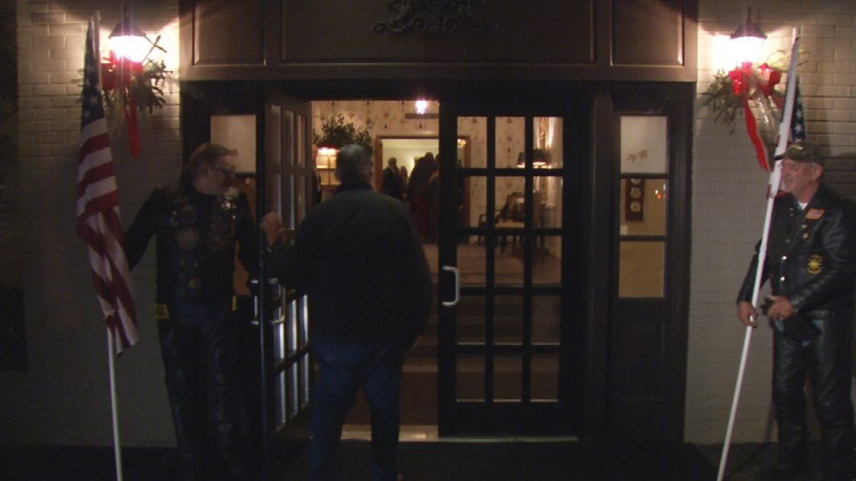 Patriot Guard Riders stand outside the doors to the funeral home to welcome guests.
