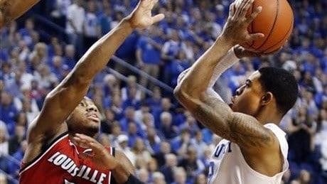 Tyler Ulis shoots over Trey Lewis in Kentucky's win over Louisville Saturday. (AP photo)