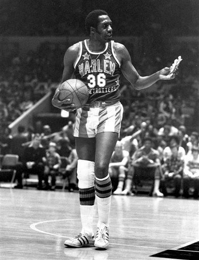 In this Feb. 18, 1978, file photo, Meadowlark Lemon, of the Harlem Globetrotters basketball team, offers a pretzel to a referee during a game at New York's Madison Square Garden.  (AP Photo/Suzanne Vlamis, File)