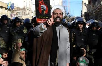 (AP Photo/Vahid Salemi). Surrounded by policemen, a Muslim cleric addresses a crowd during a demonstration to protest the execution of Saudi Shiite Sheikh Nimr al-Nimr, shown in the poster in background, in front of the Saudi embassy in Tehran.