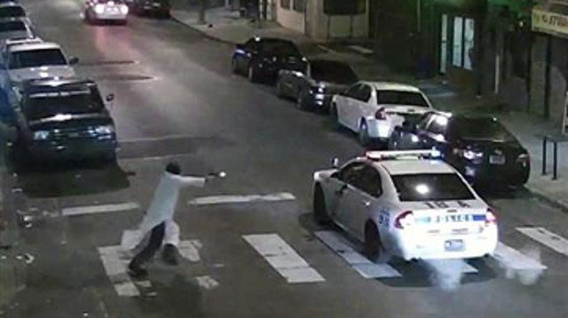 In this frame from a Thursday, Jan. 7, 2016 video provided by the Philadelphia Police Department, Edward Archer runs with a gun toward a police car driven by Officer Jesse Hartnett in Philadelphia. (Philadelphia Police Department via AP)