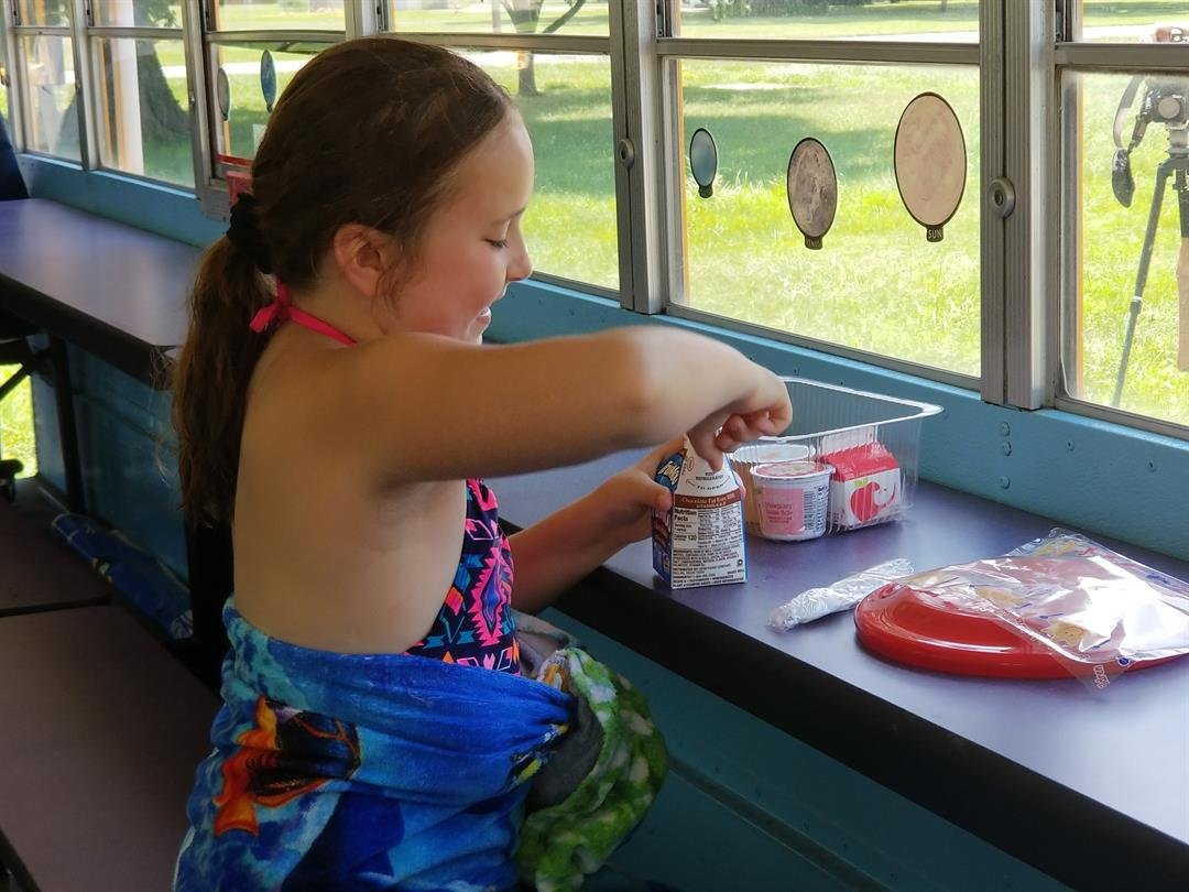 Adyson Allen, an incoming fourth-grade student at Wilt Elementary, opens a carton of milk on the Bus Stop Cafe July 9.