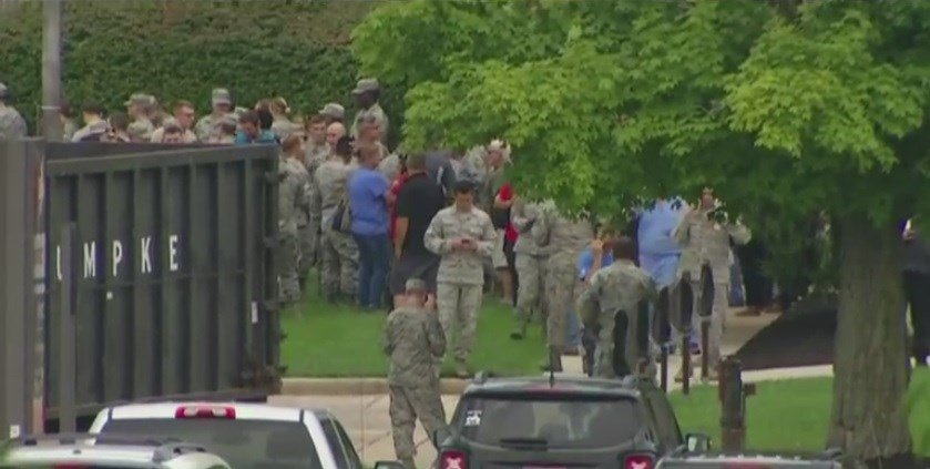 Hospital workers and military members wait outside the Wright-Patterson AFB Hospital during an active shooter situation.